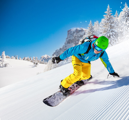 Active man snowboarder riding on slope, snowboarding closeup. Archivio Fotografico
