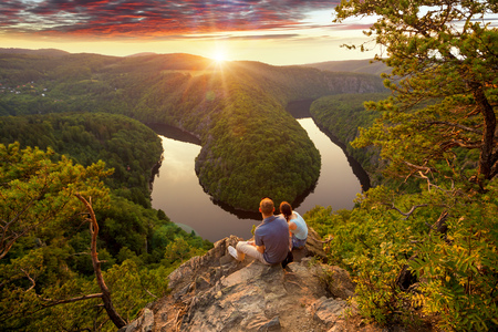 Young couple looking down the river in the beautiful mountain. Man and woman together.