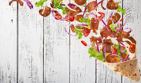 Close-up van kebab sandwich met vliegende ingrediënten. Beweging bevriezen. Stockfoto