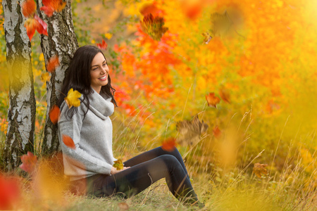 Portrait of happy young brunette woman with falling autumn leaves sitting under birch trees.