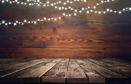 Empty wooden table with little lights for product display montages