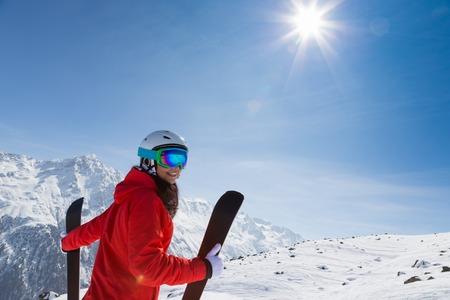 스키와 함께 아름 다운 갈색 머리 여자입니다. 겨울 동안 화창한 날입니다.