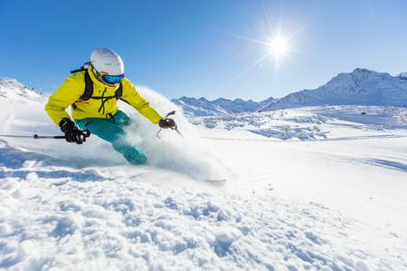 高い山の晴れた日にスキーヤーが下り坂をスキー 写真素材