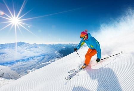 Skiërs skiën omlaag tijdens zonnige dag in hoge bergen Stockfoto