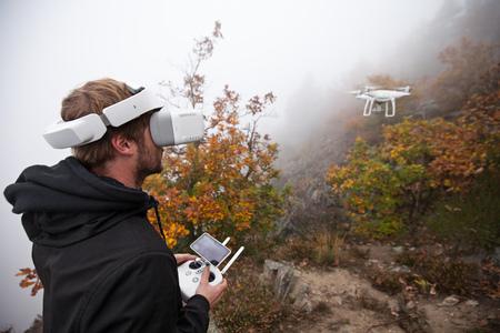 Jovem manipulando drone, usando óculos de realidade virtual. Novas tecnologias e tendências em gravação de fotos e vídeos. Foto de archivo - 94039747