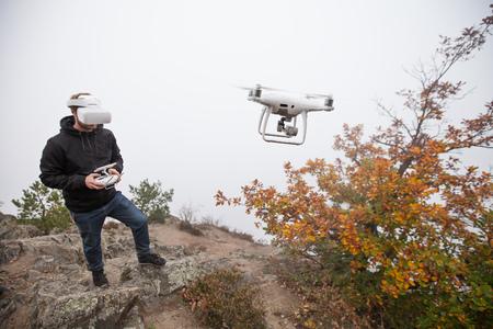 Jovem manipulando drone, usando óculos de realidade virtual. Novas tecnologias e tendências em gravação de fotos e vídeos. Foto de archivo - 94039757