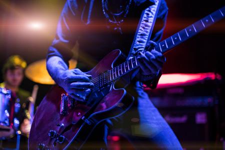 Rocker gra na gitarze na scenie.