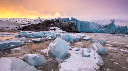 Famous Fjallsarlon glacier and lagoon with icebergs swimming on frozen water.