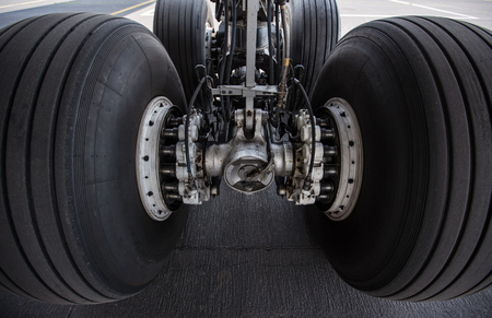 Close-up of main landing gear of modern commercial airplane standing at international airport.