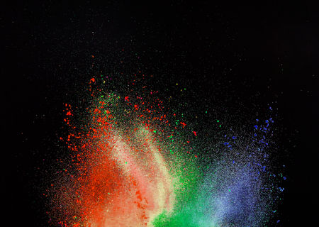 Launched colorful powder, isolated on black background, close-up.