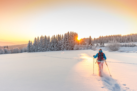 Sunny winter landscape with man on snowshoes in the mountains. 스톡 콘텐츠