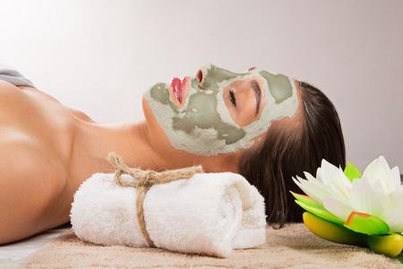 Jonge gezonde vrouw die in kuuroord behandelingen en gezichtsmasker maakt. Stockfoto