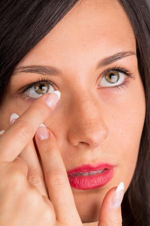 젊은여자가 그녀의 눈에 콘택트 렌즈 퍼 팅. 매크로 촬영. 스톡 콘텐츠