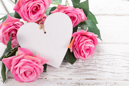 Flowers composition for Valentine's, Mother's or Women's Day. Pink flowers with wooden hearth on old white wooden background. Still-life. Reklamní fotografie