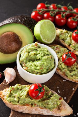 A delicious bowl of Guacamole with fresh ingredients on stone table.