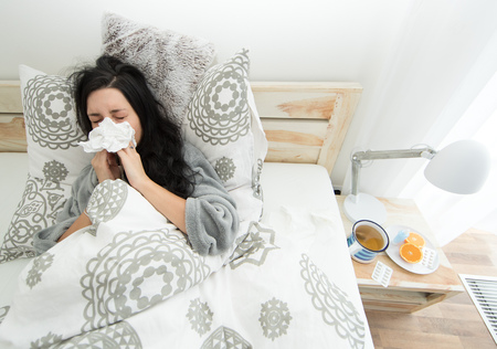 Young woman having flu, blowing her nose. Banco de Imagens - 94296117