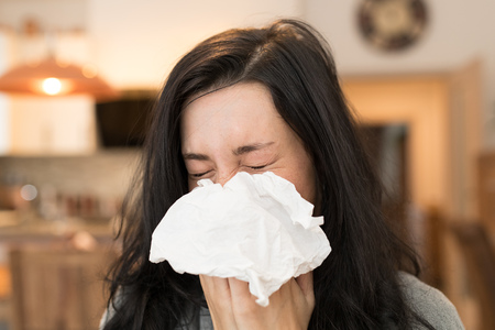 Young woman having flu, blowing her nose. Banco de Imagens - 94295956