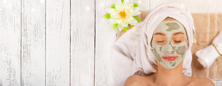 Young healthy woman with face clay mask. Stockfoto