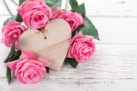 Flowers composition for Valentines, Mothers or Womens Day. Pink flowers with wooden hearth on old white wooden background. Stock Photo