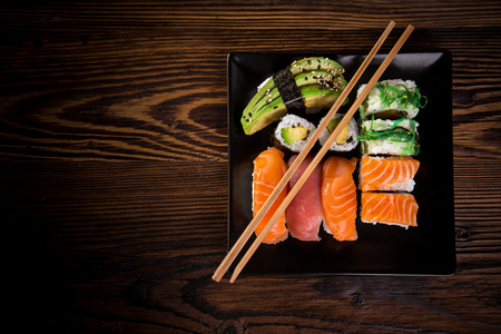 Various kinds of sushi served on wooden table, top view.