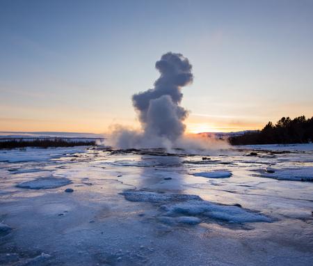 Eruption of famous Strokkur geyser in Iceland. Winter sunset.