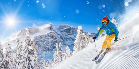 Skier on piste running downhill in beautiful Alpine landscape. Blue sky on background. Stok Fotoğraf - 97130384