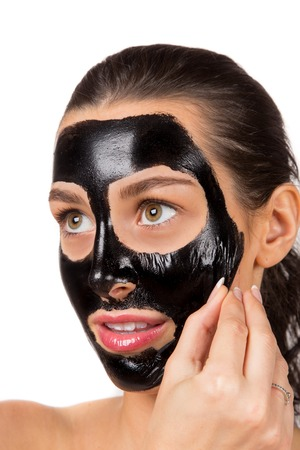 Portrait of young healthy woman with black peel face mask. Stock Photo