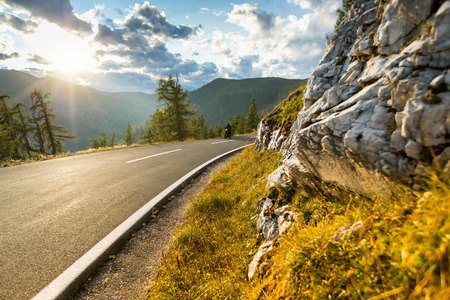 Motorcycle driver riding in Alpine highway, Nockalmstrasse, Austria, central Europe. Stock Photo