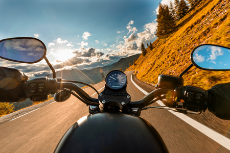 Motorcycle driver riding in Alpine highway, handlebars view, Austria, central Europe. Stock Photo