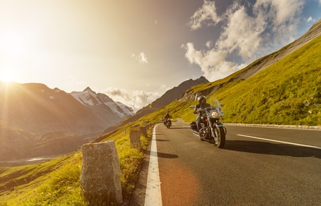 Motorcycle drivers riding in Alpine highway on famous Hochalpenstrasse, Austria, central Europe. Stock Photo