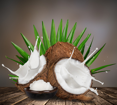 close-up of a coconuts with milk splash on old wooden background