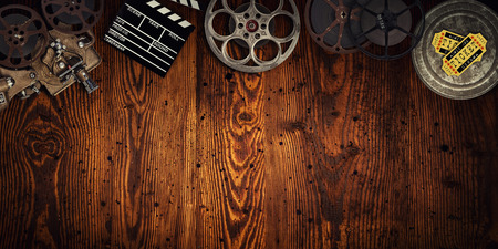 Cinema concept of vintage film reels, clapperboard and projector on old wooden background. Stock Photo - 97645551