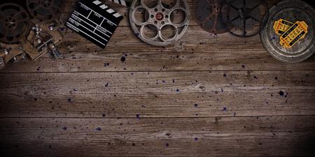 古い木製の背景にヴィンテージフィルムリール、クラッパーボードとプロジェクターのシネマコンセプト。