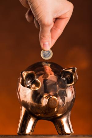 Hand putting coin money to piggy bank saving, save money concept.