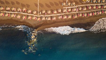 Perissa beach during sunrise on the Greek island of Santorini with sunbeds and umbrellas.