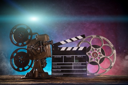 クラッパーボードとヴィンテージスチールリール、クローズアップ付きの古いスタイルの映画プロジェクター。 写真素材