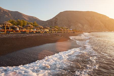 Perissa beach during sunrise on the Greek island of Santorini with sunbeds and umbrellas. Stock Photo - 97645581