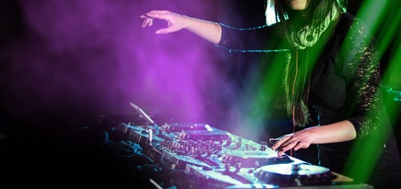 Dj mixes the track in the nightclub at a party, close-up.