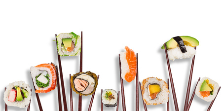 Traditional japanese sushi pieces placed between chopsticks, separated on white background. Foto de archivo