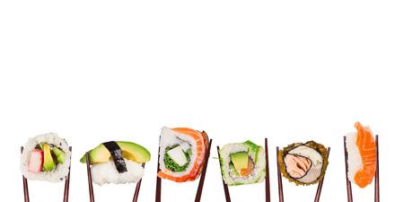 Traditionelle japanische Sushistücke platziert zwischen die Essstäbchen, getrennt auf weißem Hintergrund.
