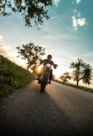 Man riding sportster motorcycle during sunset. 写真素材
