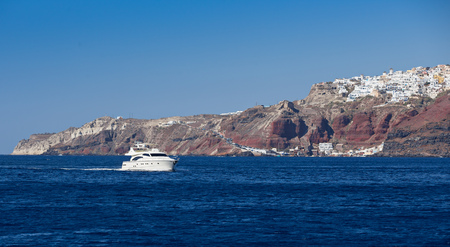 Boat in deep blue water, Santorini, Greece. Stock Photo - 99219553