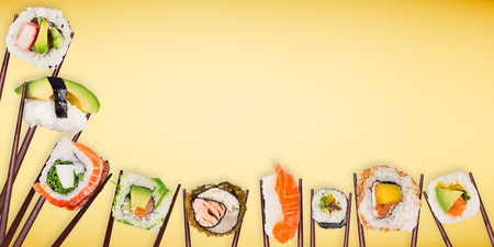 Traditional japanese sushi pieces placed between chopsticks on pastel color background. Standard-Bild - 99219716