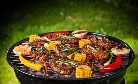 Barbecue garden grill with beef steaks, close-up. Stock Photo