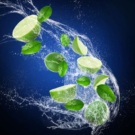 Limes with water splash on dark background