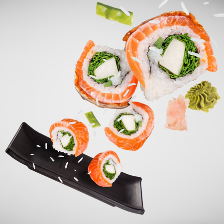 Pieces of delicious japanese sushi frozen in the air. Isolated on light grey background Standard-Bild - 100059372