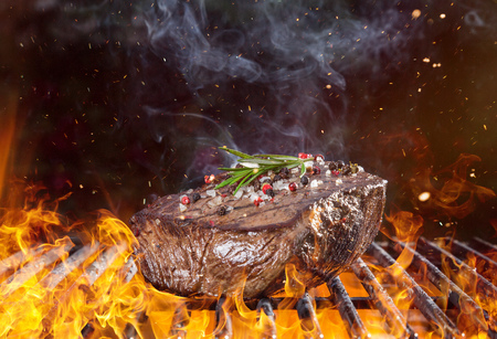 Tasty Beef steak on the grill with fire flames Stock Photo