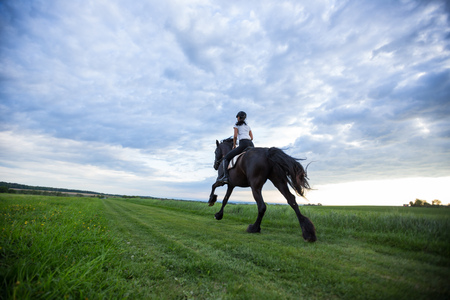 Beautiful woman riding a black friesian horse on spring meadow.