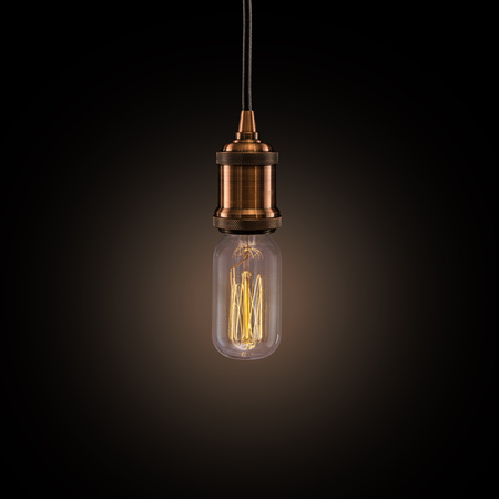 Vintage light bulb on dark background.