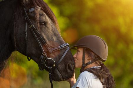 Mujer joven besando a su caballo al amanecer.
